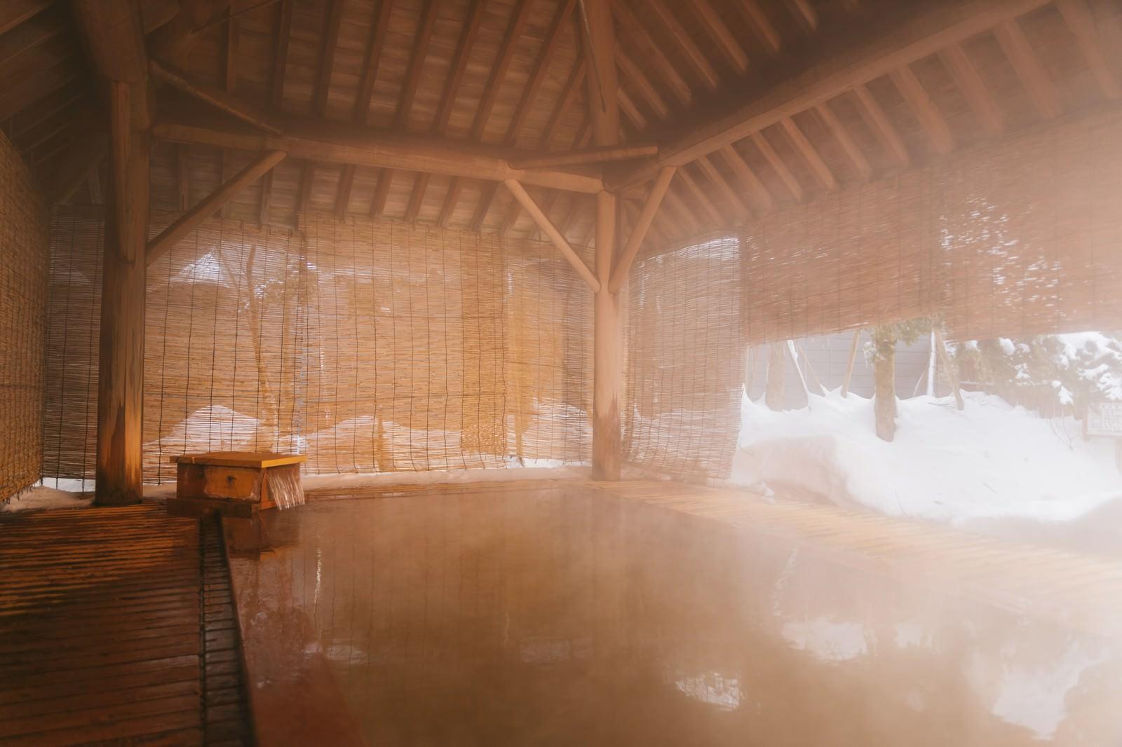 「溢れ出る温泉にざっぶーんと身を沈める平湯館の総檜露天風呂」の写真