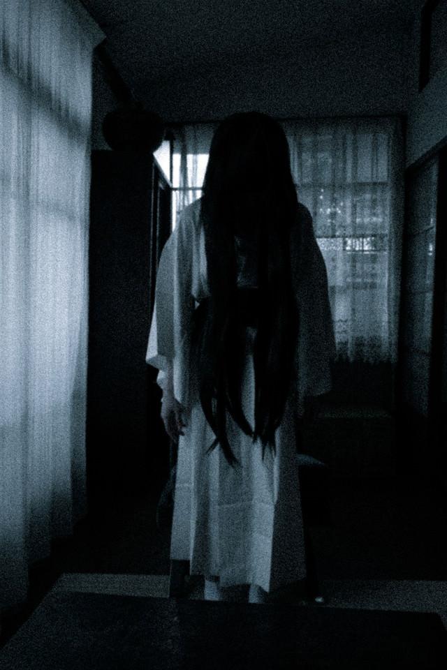 暗い室内でうつむく長髪の女の霊の写真