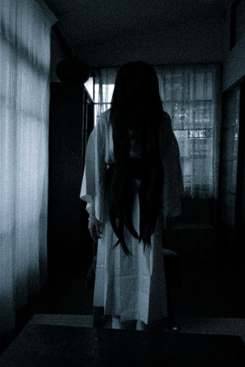 「暗い室内でうつむく長髪の女の霊」の写真[モデル:緋真煉]