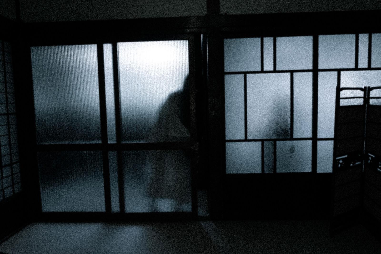 「暗い部屋に入ろうとする人影」の写真[モデル:緋真煉]