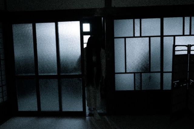 薄暗い部屋に入る黒髪長髪の女性の写真