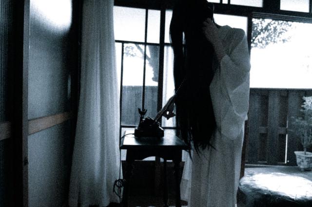 黒電話から匿名のクレームを入れる女性の写真
