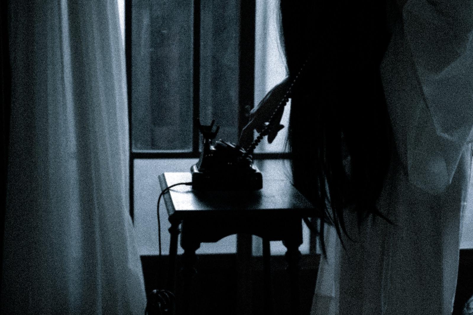 「黒電話からダイヤルする不気味な女性の姿」の写真[モデル:緋真煉]