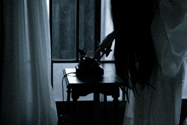 黒電話からダイヤルする不気味な女性の姿の写真