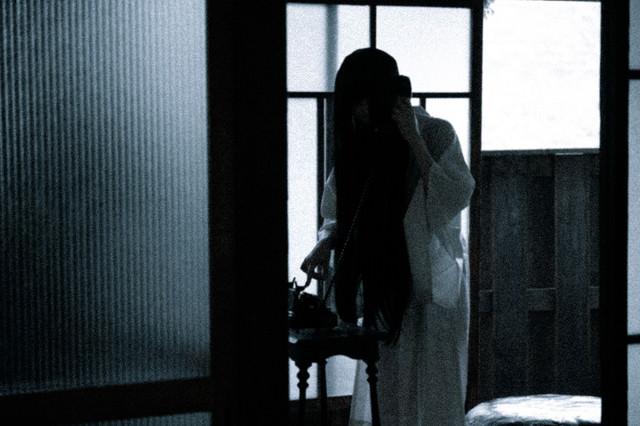 通販で買った白装束のサイズが合わないのでお客様相談室に電話する女性の写真