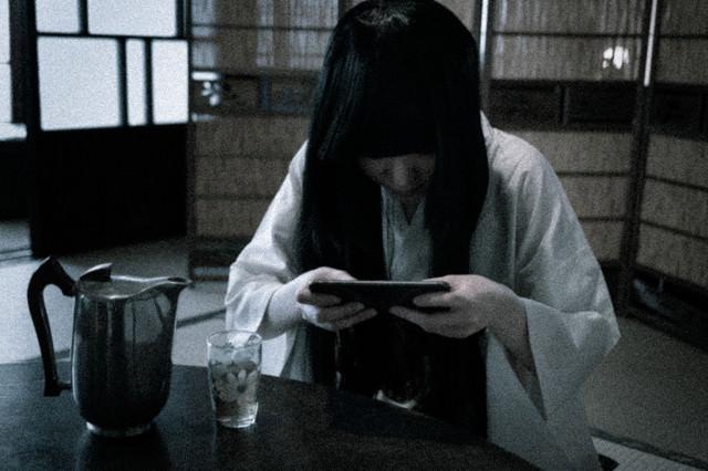 スマホゲームに夢中なサダコさんの写真