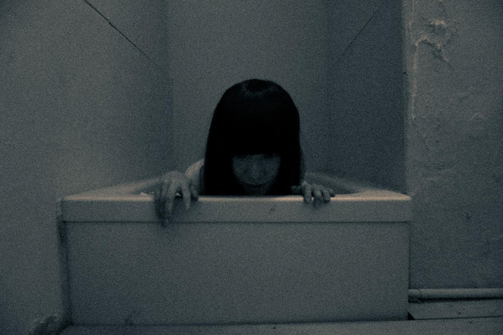 「薄暗い場所に閉じ込められる女性」の写真[モデル:緋真煉]