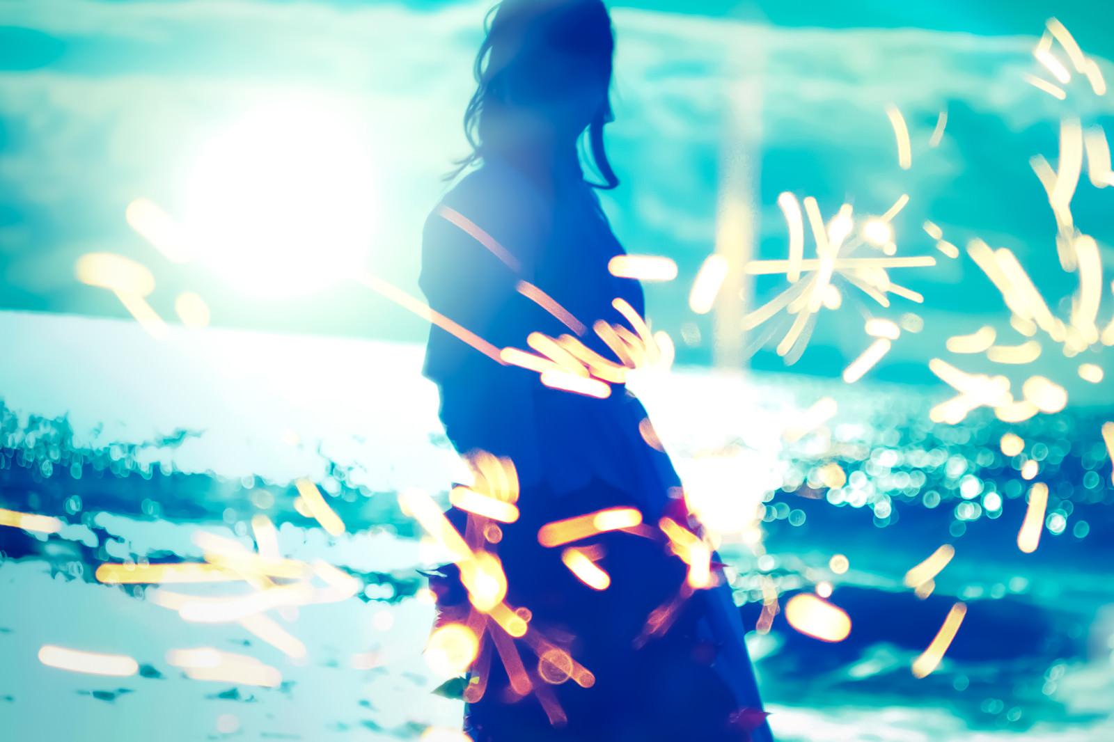 「弾ける火花と海岸の女性のシルエット」の写真[モデル:Mizuho]