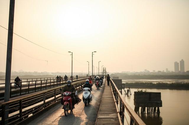 ロンビエン橋を走行するバイクとベトナムの人々の写真