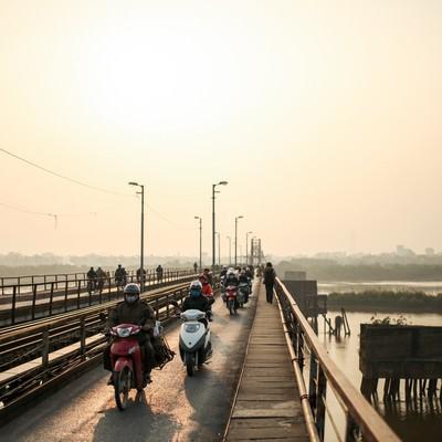 「ロンビエン橋を走行するバイクとベトナムの人々」の写真素材