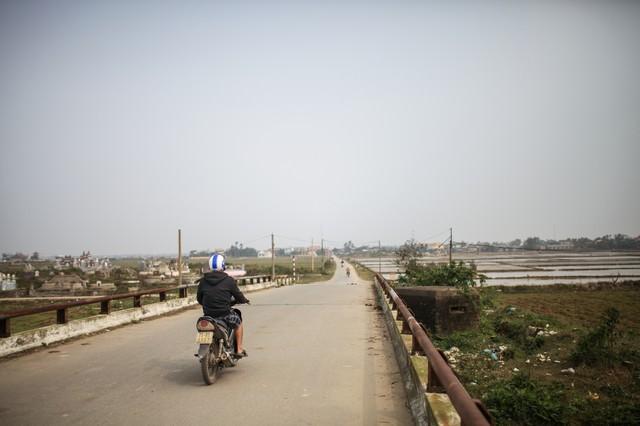 フエ(ベトナム)の田舎道と走行するバイクの写真