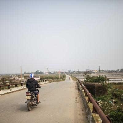 「フエ(ベトナム)の田舎道と走行するバイク」の写真素材