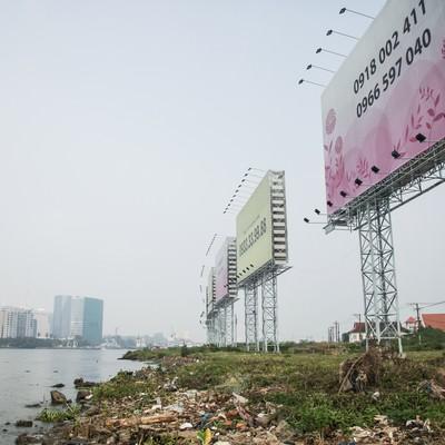 「ホーチミンの沿岸のゴミと広告看板」の写真素材