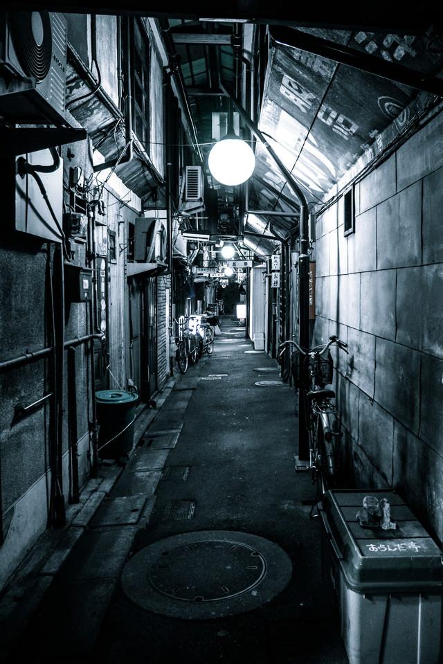 路地裏の道を照らす灯りの写真