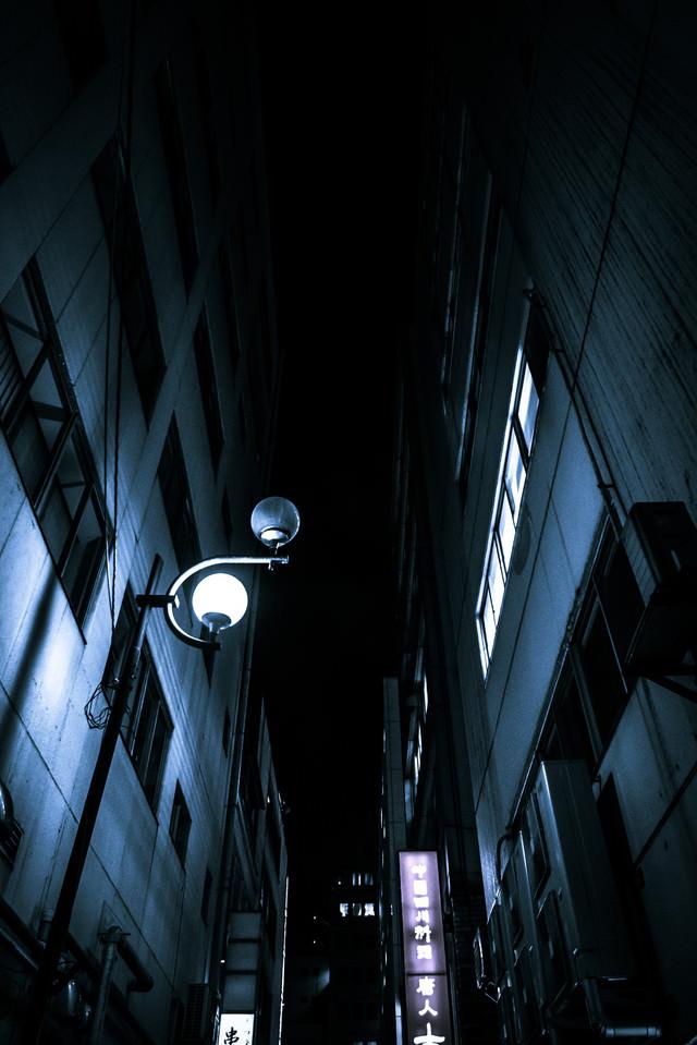 夜間のビルとビルの隙間の写真