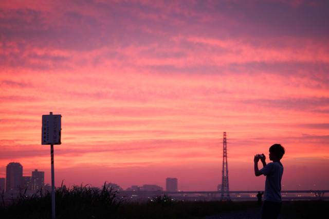 夕焼け空を撮影する少年の写真