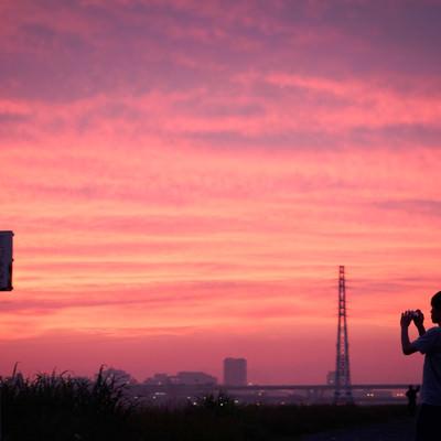 「夕焼け空を撮影する少年」の写真素材