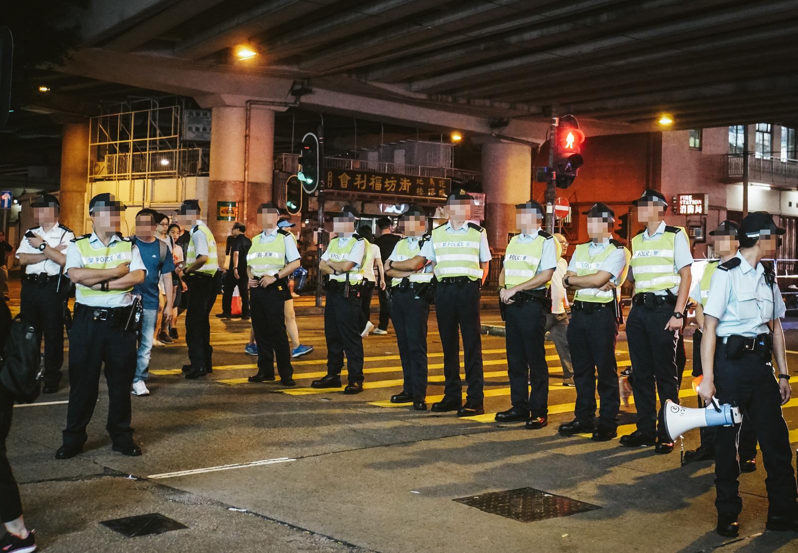 「香港デモで道を塞ぐ警察官」の写真