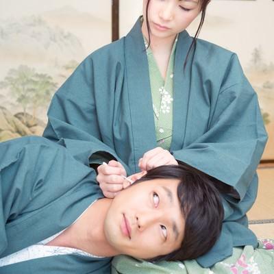 「彼女の膝枕で耳かきを堪能する彼」の写真素材