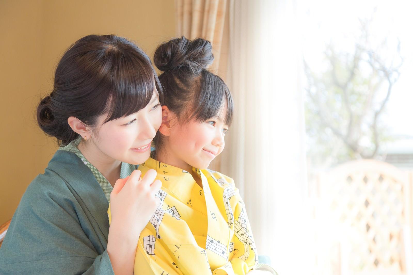 「温泉旅館の客室から庭先を眺める親子」の写真[モデル:伊藤里織]
