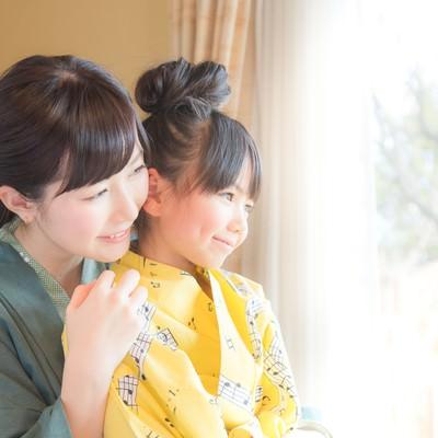 「温泉旅館の客室から庭先を眺める親子」の写真素材