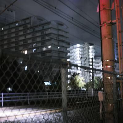 深夜の線路とフェンスの写真
