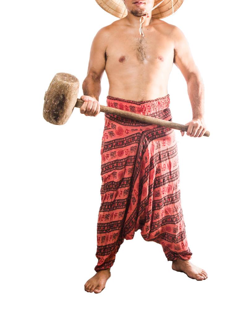 「木槌を持って前に立ちはだかる民族衣装の男性」の写真