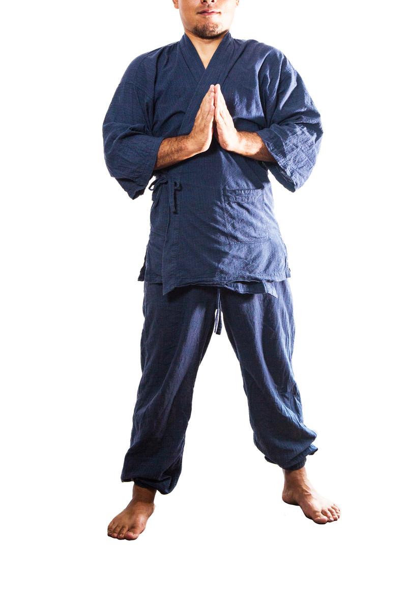 「道着に袖を通し合掌する男性」の写真