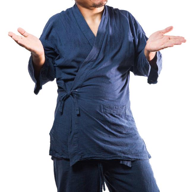 お手上げ状態の作務衣を着た男性の写真