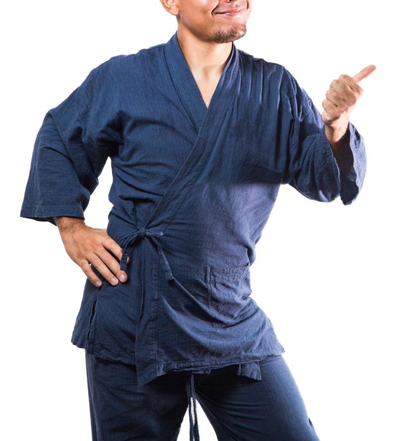 「一本勝ちした生徒にグッジョブする柔道部師範の男性」の写真