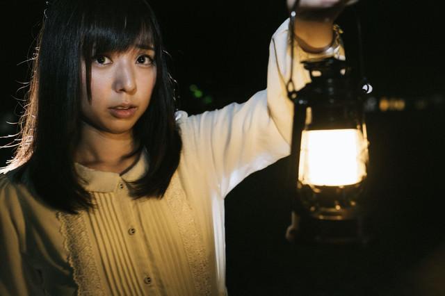 ランタンを片手に暗闇を歩く不安そうな表情の女性の写真