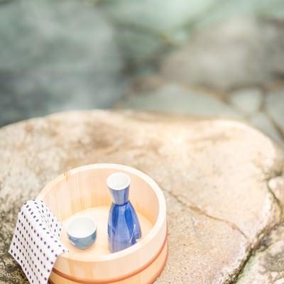 「露天風呂と桶に入ったとっくりとおちょこ」の写真素材