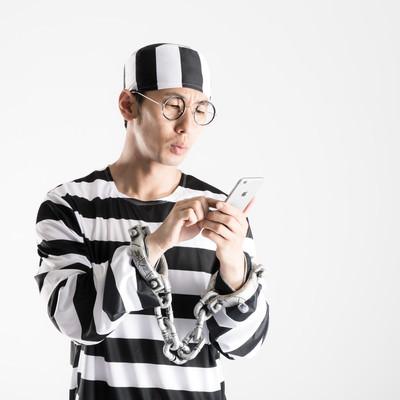 「「刑務所なう」とつぶやく囚人」の写真素材