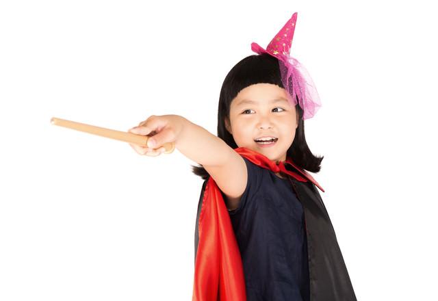 魔法をかけるハロウィン衣装の女の子の写真
