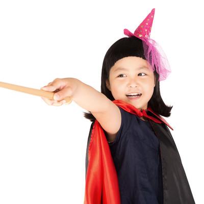 「魔法をかけるハロウィン衣装の女の子」の写真素材