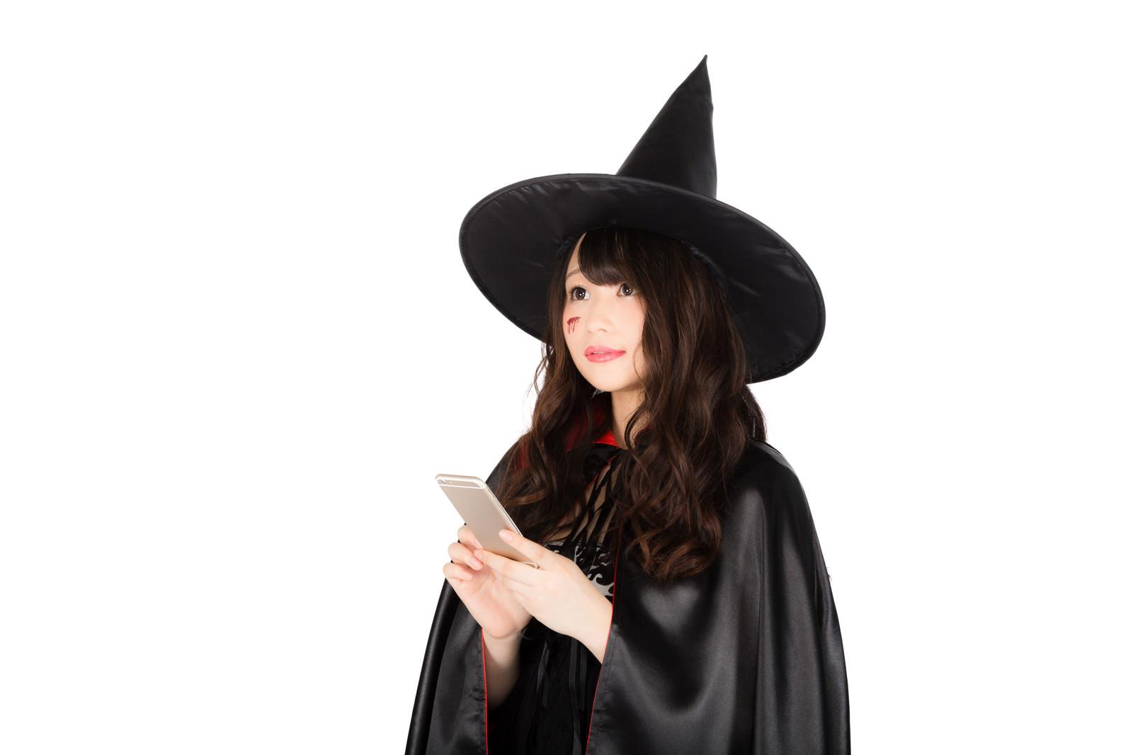 「魔法を掛ける相手をスマホの地図アプリで探す美女黒魔道士」の写真[モデル:茜さや]