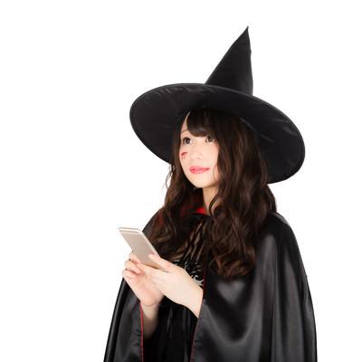 「魔法を掛ける相手をスマホの地図アプリで探す美女黒魔道士」の写真素材