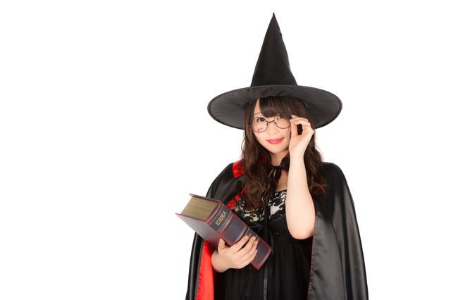 魔法書を持ったとんがり帽子のメガネ美女の写真