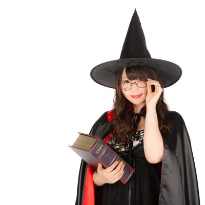 「魔法書を持ったとんがり帽子のメガネ美女」の写真素材