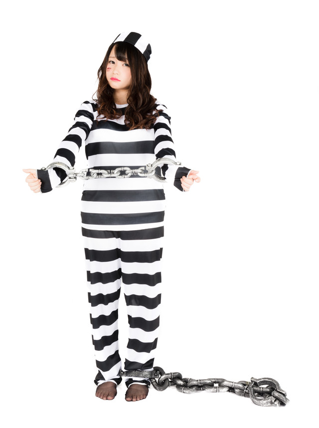 両手・両足を鎖で拘束されてしまった囚人服の美女の写真