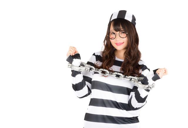 鎖に繋がれても笑顔な囚人服を着こなす美女の写真