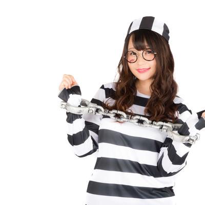 「鎖に繋がれても笑顔な囚人服を着こなす美女」の写真素材
