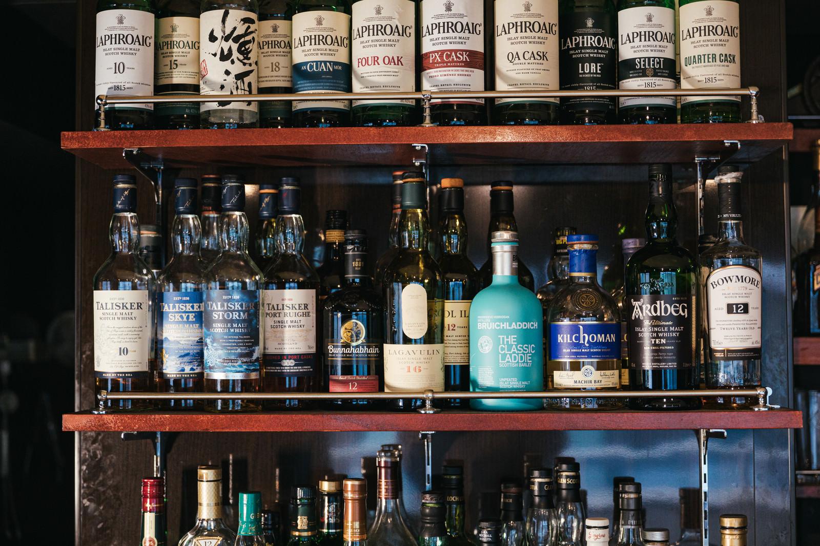 「シングルモルトウイスキーやスコッチウイスキーなどのアイラモルト勢揃いの酒棚」の写真
