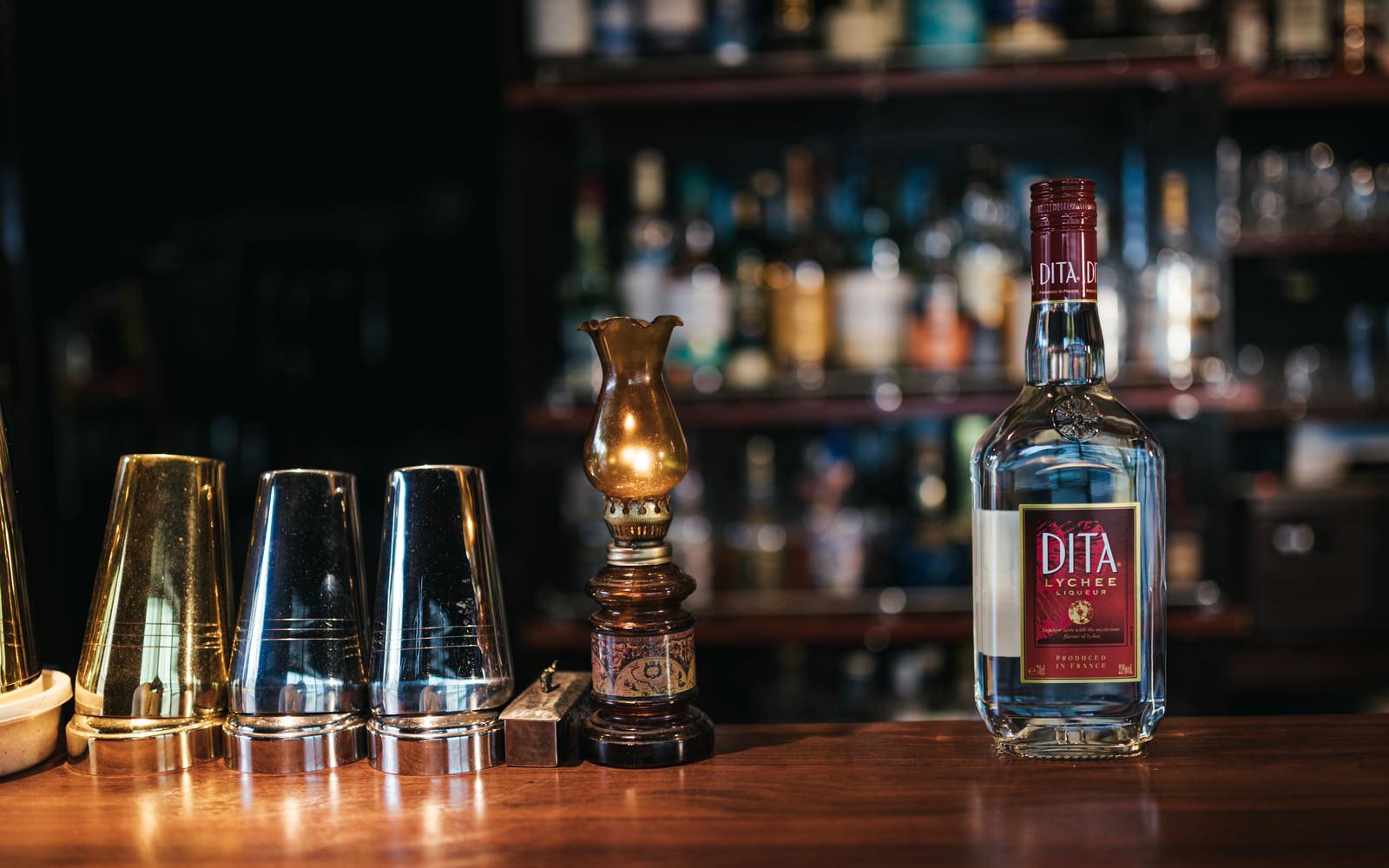 「バーカクテルの定番ライチのリキュール、ディタのボトルとバーカウンター」の写真