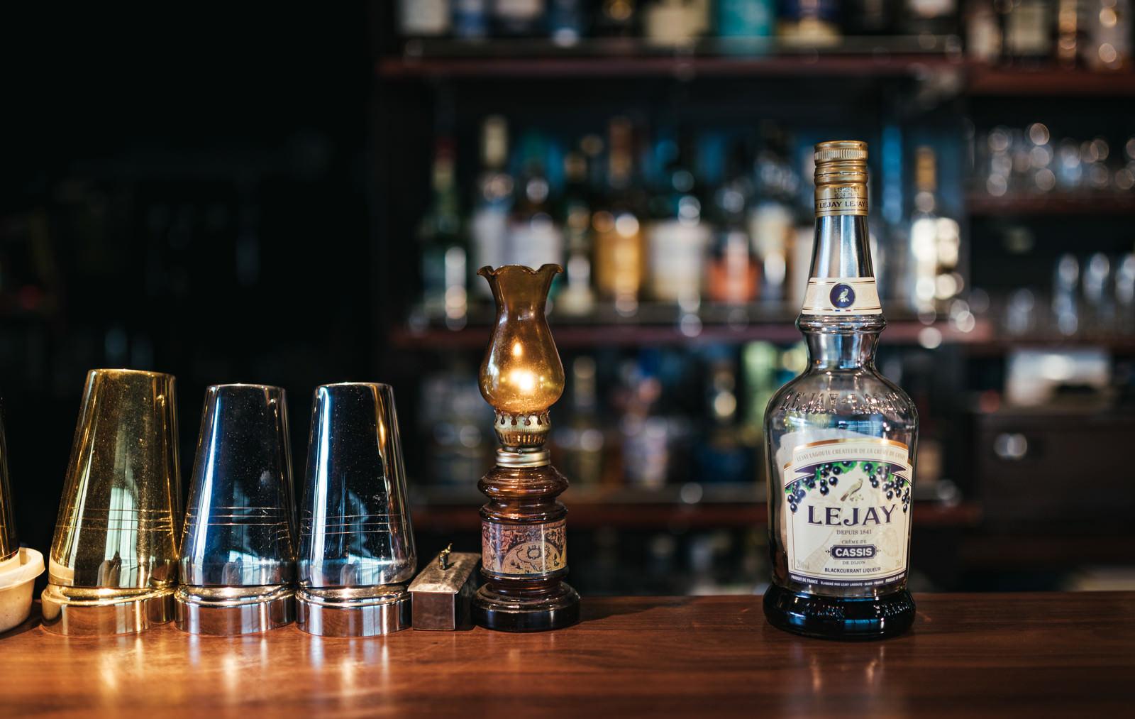 「くびれた特徴的なボトルの黒スグリのリキュール、ルジェクレームドカシスとバーカウンター」の写真