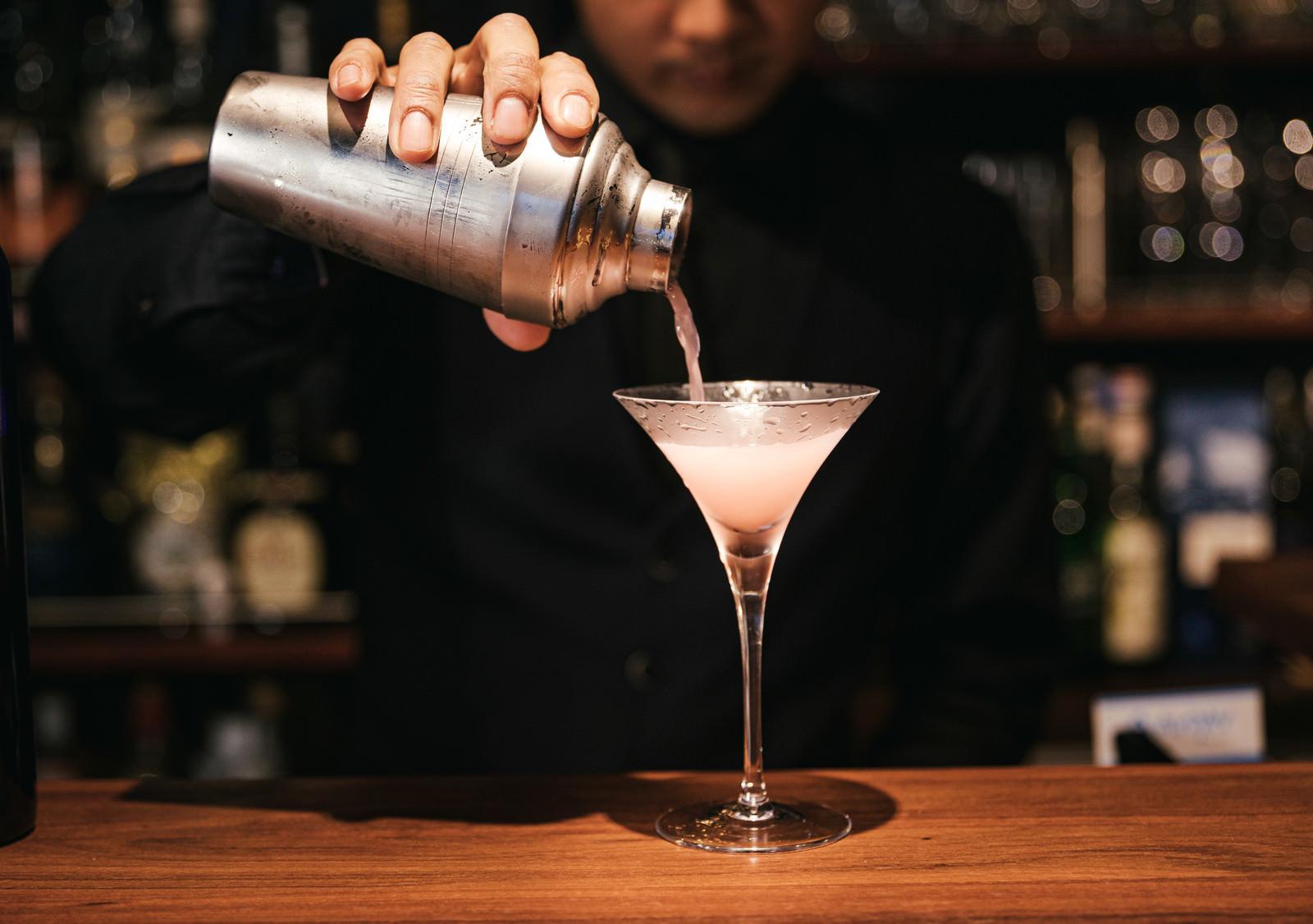 「コスモポリタンカクテルをシェーカーからグラスに注ぐバーテンダー」の写真