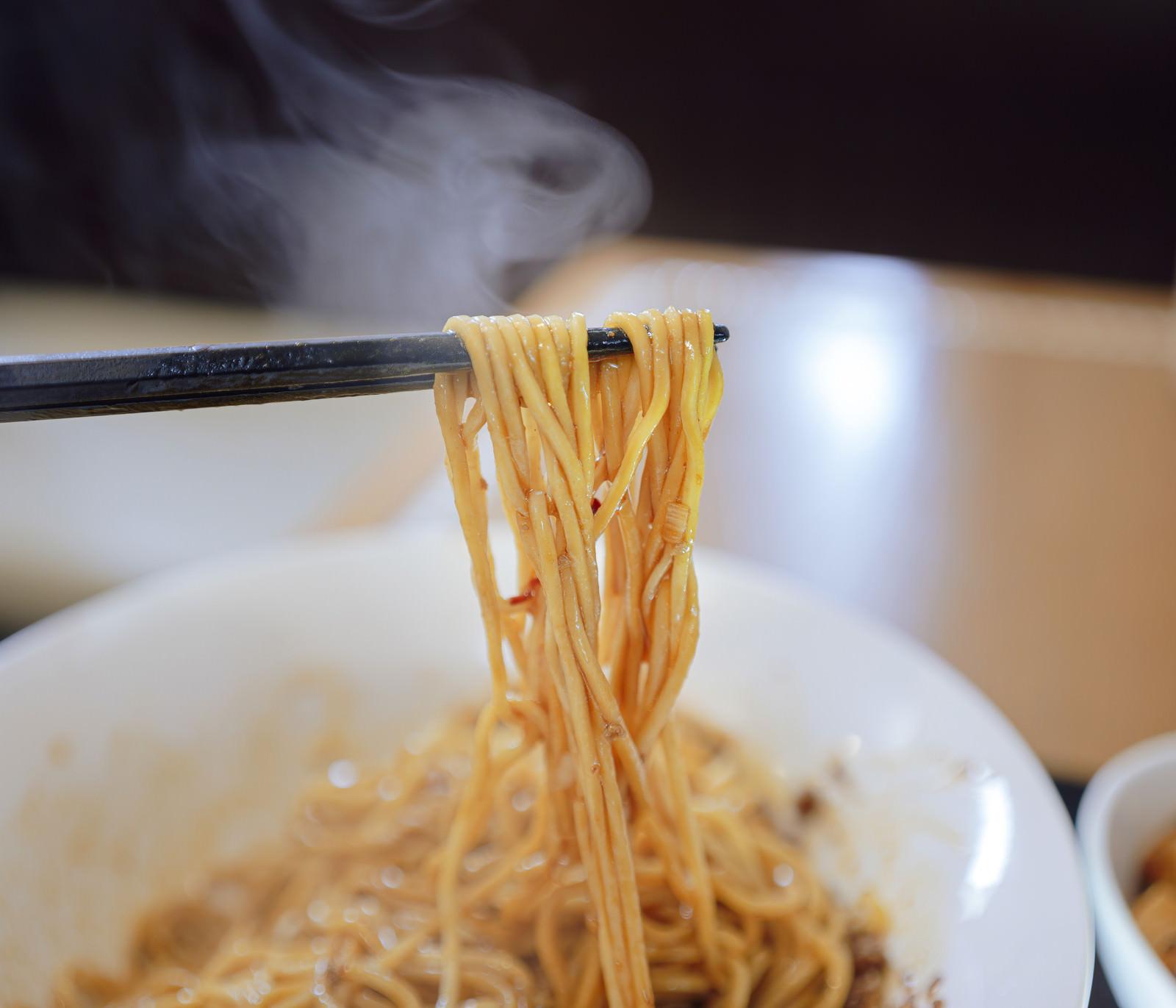 「熱々の汁なし担々麺を箸で持ち上げる」の写真
