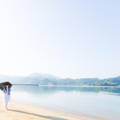 穏やかなイマリンビーチを歩く日傘女子の写真