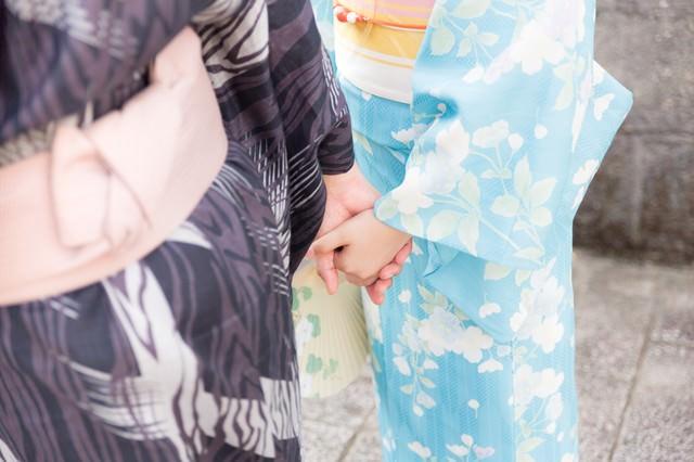 手を握り合う浴衣姿のカップルの写真