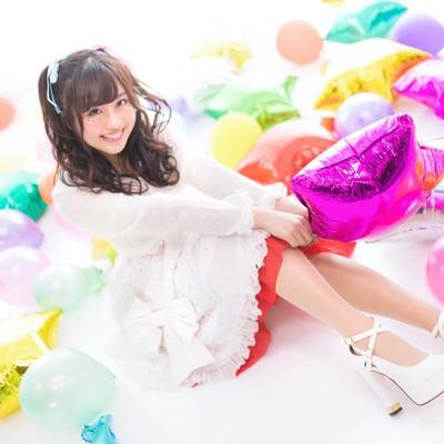 カラフルな風船に囲まれる女性アイドルの写真